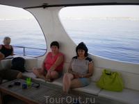 На яхте взрослые разместились на диванчиках под навесом.