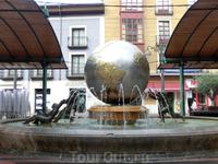 В центре площади - фонтан, представляющий земной шар, рядом с которым тоже странные скульптурные человечки.