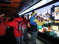 Молодёжь и туристы толпятся возле интерактивной рекламы и карты города.