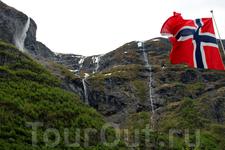 Норвежский флаг на фоне горных водопадов в Гудвангене Kjelfossen Waterfall
