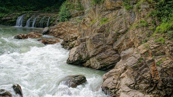 """Уже оказавшись на мосту,человека охватывает невольный трепет,так поражает мощь и красота реки Белой.Огромные,плоские каменные глыбы лежат по краям водного потока,словно пытаясь сжать его в свои тиски.  С моста виден водопад""""Три братца"""",в том месте,где ..."""