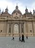 Южный фасад базилики выходит на площадь.  Первая церковь, посвященная Богородице, появилась на этом месте еще в IX веке, ко времени завоевания королем ...